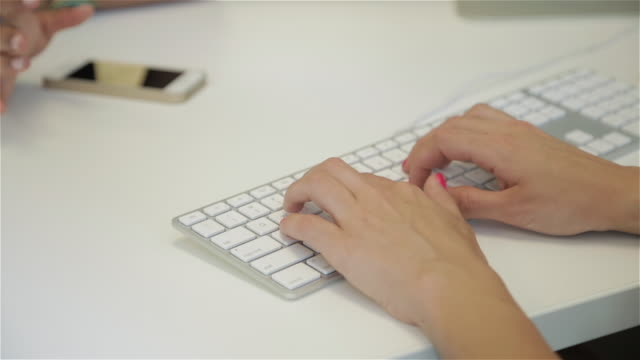 close up of female typing on computer while talking to female colleague - computer keyboard stock videos and b-roll footage