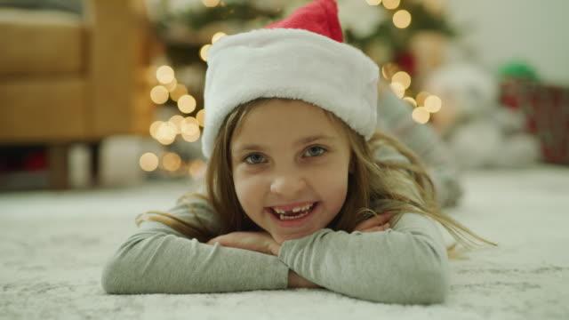 close up of festive girl wearing santa hat laying on floor on christmas / vineyard, utah, united states - santa hat stock videos & royalty-free footage