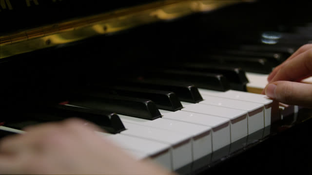 close up of fingers as they play chords on a piano - ピアノ点の映像素材/bロール