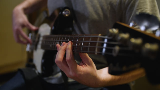 close up of fingers moving across an electric bass guitar fretboard - bass guitar stock videos & royalty-free footage