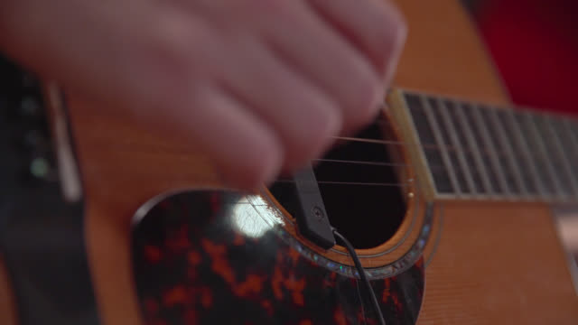 Close up of fingers picking an acoustic guitar