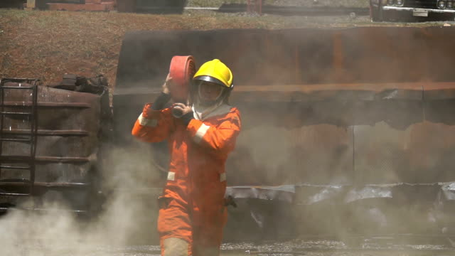 vidéos et rushes de fermez-vous vers le haut du pompier retenant le tuyau d'incendie et marchant par la fumée pour éteindre un incendie - lenteur