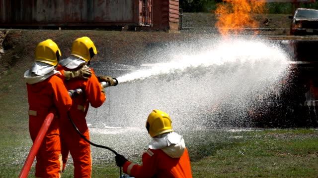 vídeos de stock, filmes e b-roll de feche acima dos sapadores-bombeiros que lutam um incêndio com a mangueira do incêndio e a espuma químicas para extinguir um incêndio do acidente do caminhão - perigo
