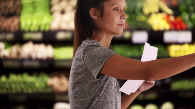 vidéos et rushes de close up of fit and healthy female customer in grocery store choosing produce - atteindre