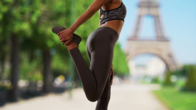 stockvideo's en b-roll-footage met close up of fit black woman athlete in paris stretching her leg - jogster