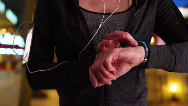 stockvideo's en b-roll-footage met close up of fit senior woman using activity tracker - jogster