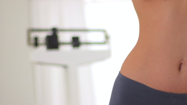 close up of fit woman with scale in background - hüfte stock-videos und b-roll-filmmaterial