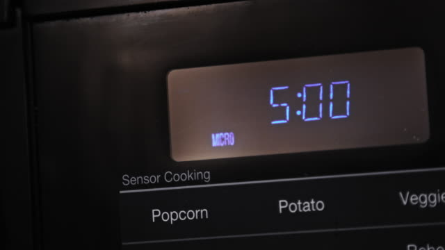 close up of five minutes entered and counting down cooking time on a black digital display microwave - timer stock videos & royalty-free footage