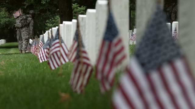vídeos de stock e filmes b-roll de close up of flags at cemetery members of the 3rd us infantry regiment the old guard participate in a flagsin ceremony at arlington national cemetery... - cemitério nacional de arlington