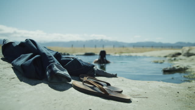 close up of flipflops and jeans with woman skinny dipping in background / meadow, utah, united states - skinny dipping stock videos & royalty-free footage
