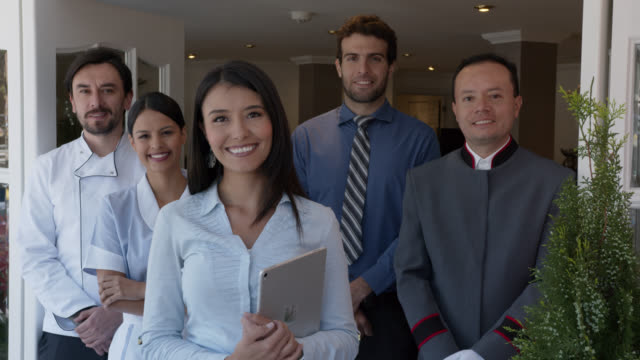 close up of friendly team of workers at a hotel all facing camera smiling - hotel stock videos & royalty-free footage