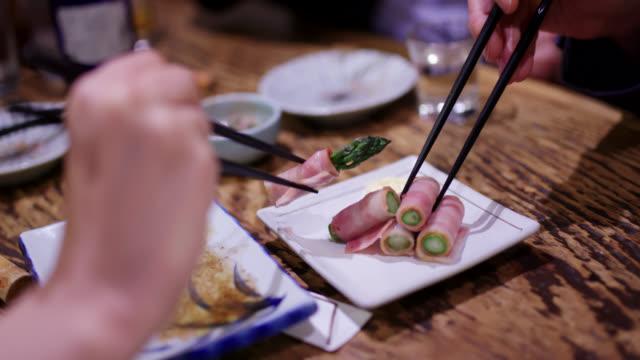 日本の伝統的な居酒屋で食べ物を食べる友人のクローズアップ - 居酒屋点の映像素材/bロール