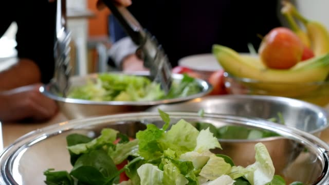 close up of friends making salad from fresh vegetables in kitchen - salad stock videos & royalty-free footage
