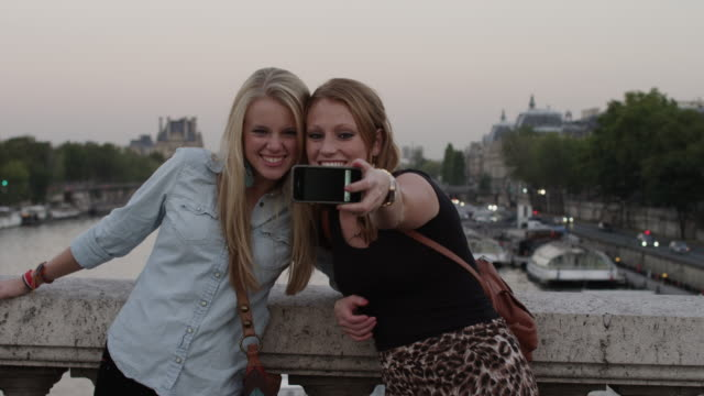 Close up of friends taking self-portrait on bridge / Paris, France