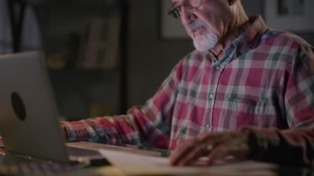 vidéos et rushes de close up of frustrated older man with paperwork and laptop at night / cedar hills, utah, united states - seniornaute