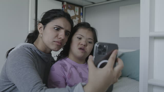 close up of girl and sister with down syndrome posing for cell phone selfies / lehi, utah, united states - sibling stock videos & royalty-free footage