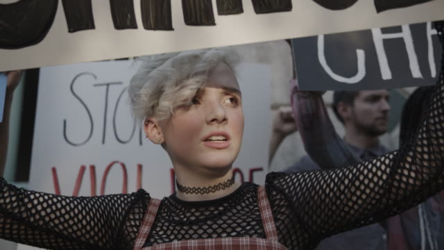 close up of girl at protest holding sign and chanting for change / provo, utah, united states - politica video stock e b–roll