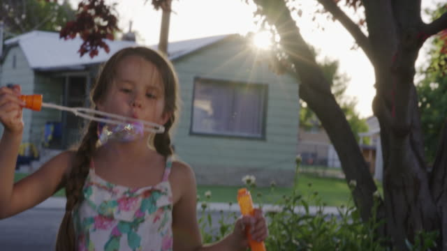 Close up of girl blowing bubbles on sunny day / Orem, Utah, United States