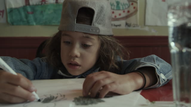 close up of girl coloring on paper with marker in restaurant / san francisco, california, united states - baseballmütze stock-videos und b-roll-filmmaterial
