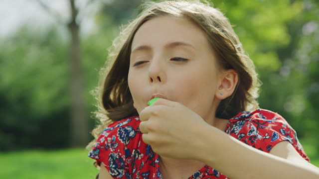 vidéos et rushes de close up of girl eating green flavored ice treat  / pleasant grove, utah, united states - yeux fermés