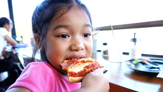 Close up of girl eating slice of pizza.