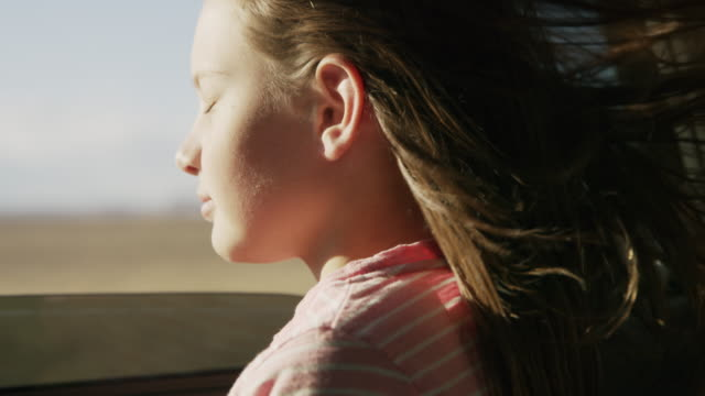 vídeos de stock, filmes e b-roll de close up of girl in car leaning out car window enjoying wind blowing hair / hanksville, utah, united states - olhos fechados