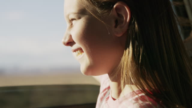 close up of girl in car with arm outstretched enjoying wind / hanksville, utah, united states - fenster stock-videos und b-roll-filmmaterial