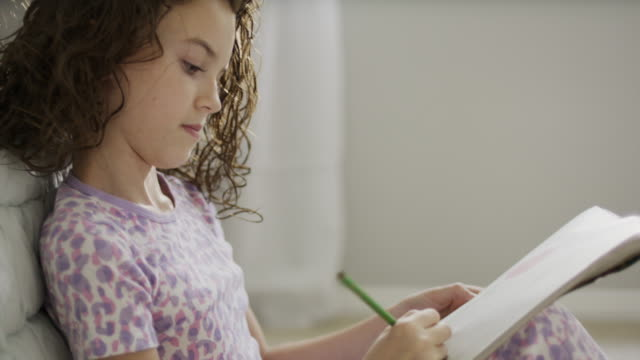 close up of girl on bed drawing on sketchpad / provo, utah, united states - provo stock-videos und b-roll-filmmaterial