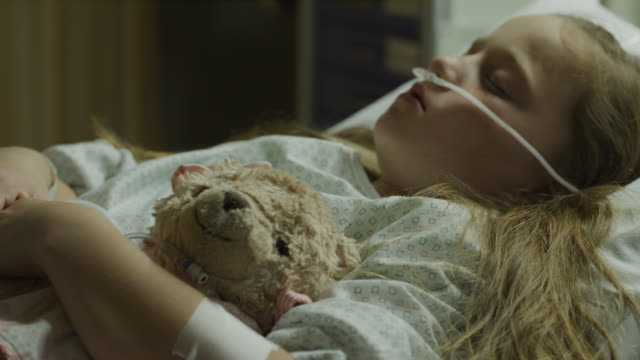 close up of girl patient sleeping in hospital bed holding teddy bear / salt lake city, utah, united states - テディベア点の映像素材/bロール