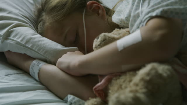 close up of girl patient sleeping in hospital bed with teddy bear / salt lake city, utah, united states - 横たわる点の映像素材/bロール