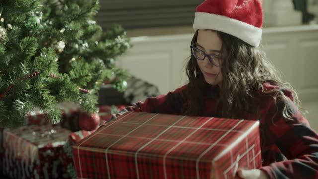 close up of girl peeking under wrapping paper of christmas gift / orem, utah, united states - orem utah stock videos & royalty-free footage