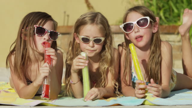 Close up of girls eating flavored ice at poolside / Cedar Hills, Utah, United States