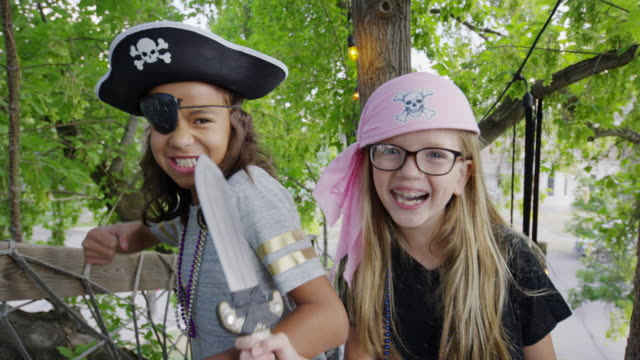 Close up of girls holding swords playing pirate in tree / Provo, Utah, United States