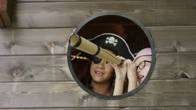 Close up of girls playing pirate in window using telescope / Provo, Utah, United States