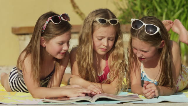 close up of girls reading magazine at poolside / cedar hills, utah, united states - only girls stock videos and b-roll footage