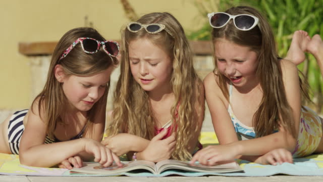 close up of girls reading magazine at poolside / cedar hills, utah, united states - poolside stock videos and b-roll footage