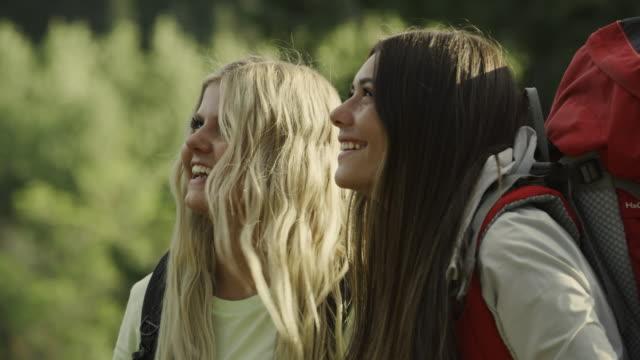 close up of girls sharing binoculars in forest / tibble fork, utah, united states - neugierde stock-videos und b-roll-filmmaterial