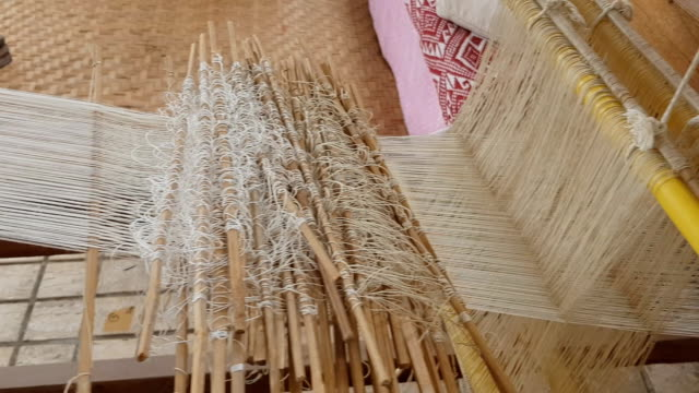vídeos de stock e filmes b-roll de close up of gold silk weaving on loom, cotton on the manual wood loom in asian traditional culture and woman hand weave lifestyle - bambu material