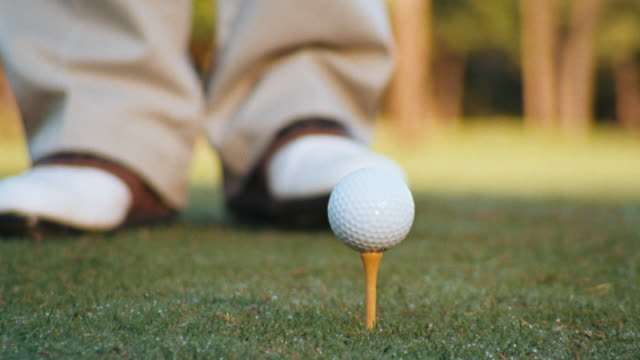 close up of golf ball on a tee, as a man's golf shoes step into frame with a large wood driver as he prepares for tee-off shot. - golf shoe stock videos & royalty-free footage