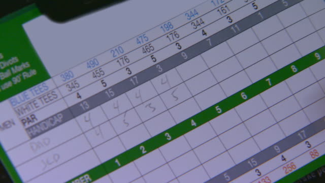 close up of golf score card and someone writing in scores - 得点する点の映像素材/bロール
