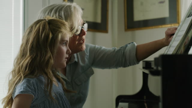 stockvideo's en b-roll-footage met close up of grandmother teaching granddaughter to play piano / pleasant grove, utah, united states - differential focus