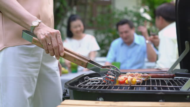 close up of grilled barbecue with family in the garden. - barbecue social gathering stock videos & royalty-free footage