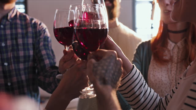 Close up of group of friends toasting with red wine.