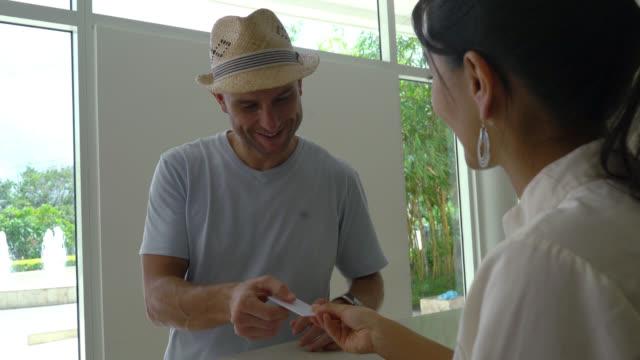 vídeos de stock, filmes e b-roll de close-up de comentários chegar ao hotel para check-in e receber a chave de cartão - recepcionista
