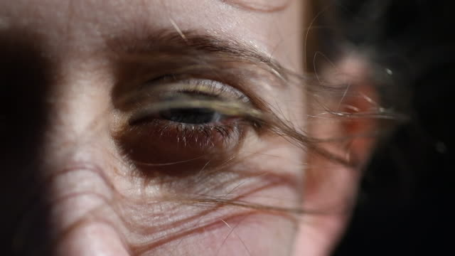 close up of hair blowing in a young girls eye - windswept stock videos & royalty-free footage