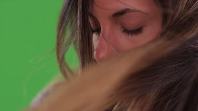 stockvideo's en b-roll-footage met close up of hair blowing in face of serious millennial woman on greenscreen - natuurlijk haar