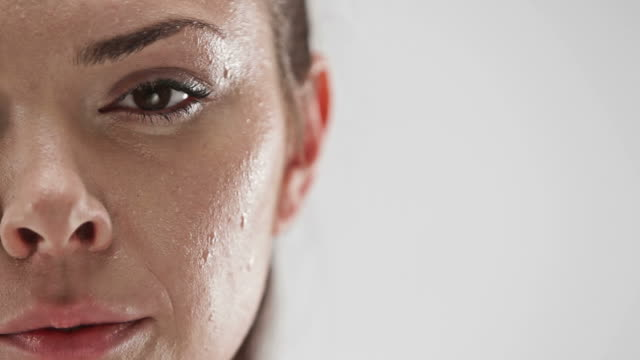 Close up of half of face of athletic caucasian woman sweating and looking at camera