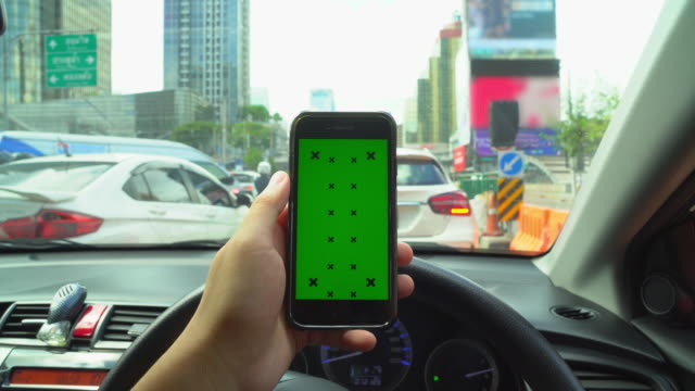 close up of hand handheld smart phone looking at green screen chroma key display in car. using mobile phone by scrolling, swipe, finger to touch screen. - smart automobile brand stock videos and b-roll footage