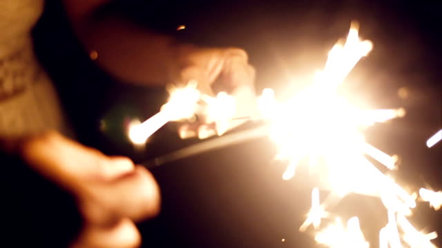close up of hand holding sparkler - luminosità video stock e b–roll