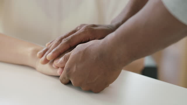 close up of hand men black african ethnicity holding hands and touching of female caucasian ethnicity talking sharing and solution together.care,mental health,helping hands concept - emotional support stock videos & royalty-free footage